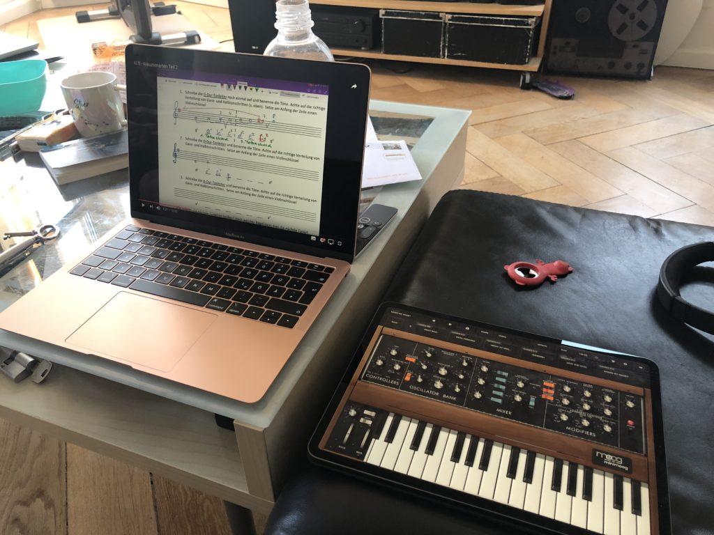 MacBook zeigt den Film des Lehrers, iPad liegt als Klavierersatz daneben